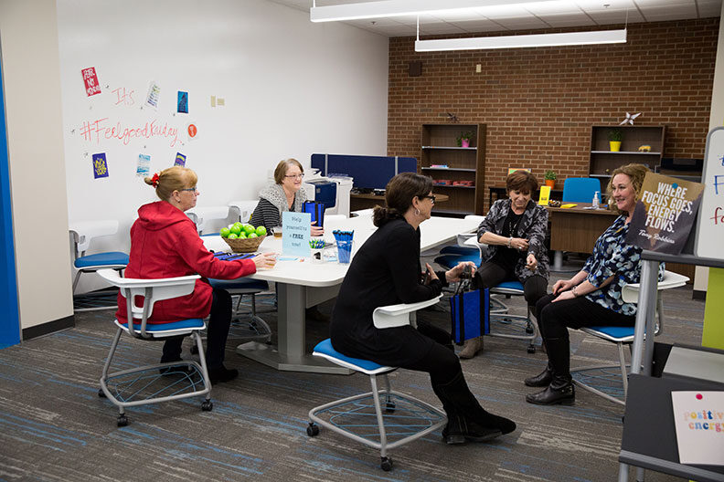 A group of staff sit together inside the Elmhurst University Learning Center for academic support.