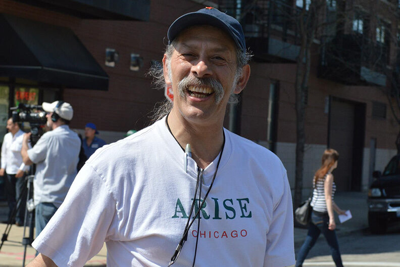 Jorge Mujica smiling wearing Arise Chicago tshirt.