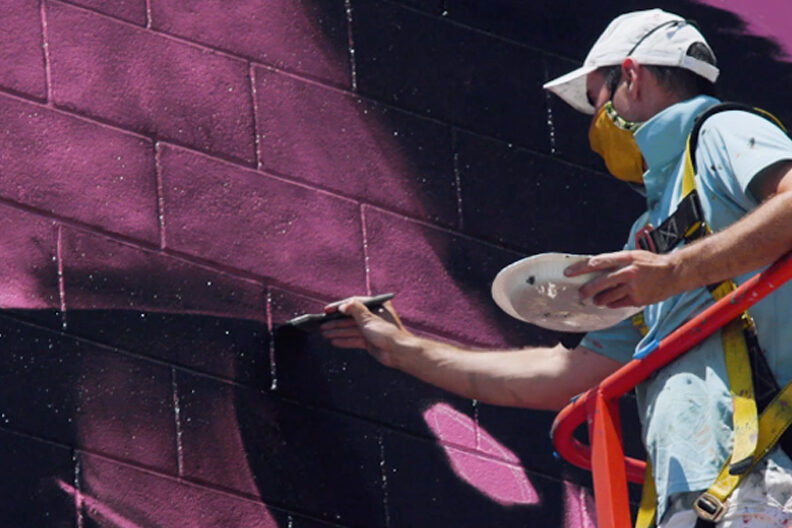 Muralist and Elmhurst University art professor Rafael Blanco, wearing a white baseball cap, paints a mural on the campus of his alma mater, the University of Nevada-Reno.