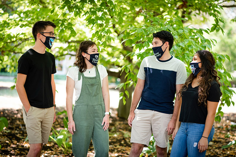 Four Elmhurst University students, two male and two female, talk with each other while wearing face masks with the university logo on them.