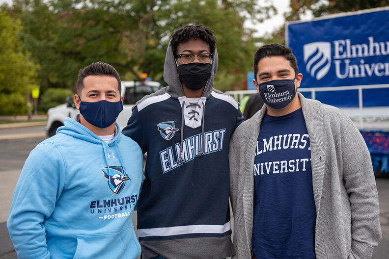 Three students wearing Elmhurst University spirit wear at the Homecoming Parade.