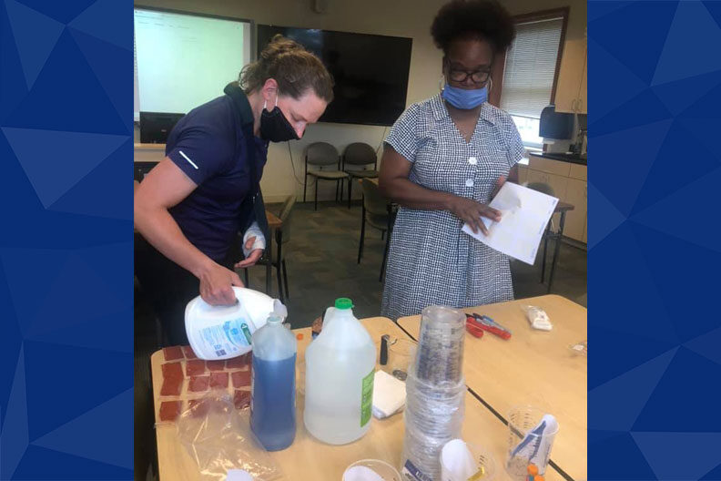 Two Elmhurst University faculty members standing over a table prepare STEM kits for students.
