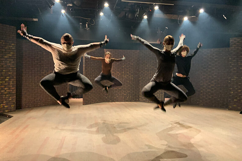 Four dance students jumping in the air while performing their dance routine in the Elmhurst University Mill Theatre.