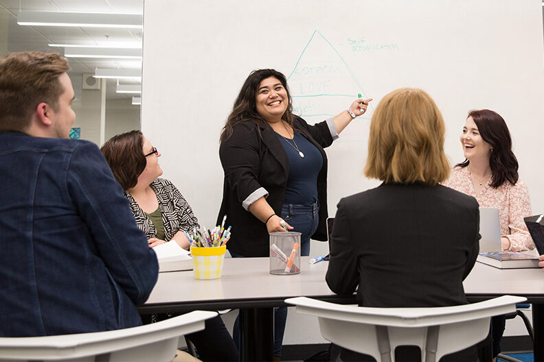 A woman stands at the front of the class and points to a whiteboard.