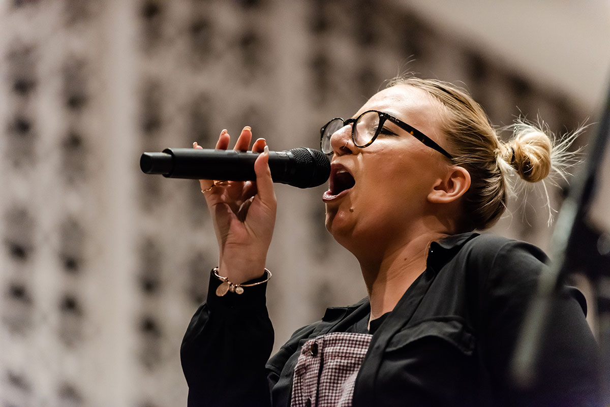 A female student sings into a microphone during the Elmhurst University Jazz Festival.