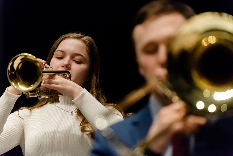 A female Elmhurst University student (background) plays the trumpet alongside a male student (foreground) playing the trombone in the University's Jazz Band.