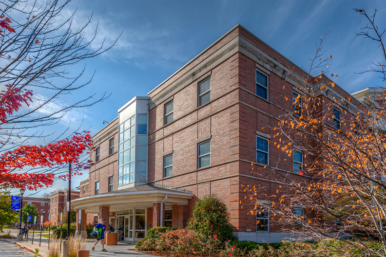 An exterior photo of Circle Hall with a student walking outside.