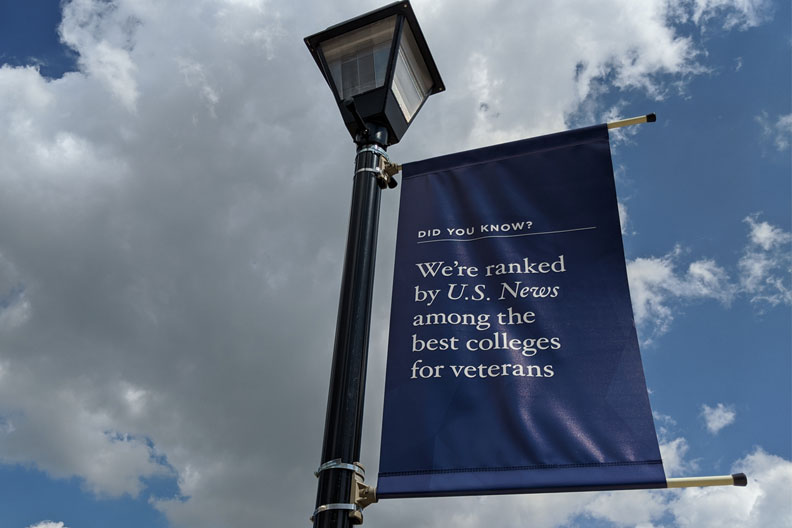 A blue Elmhurst University banner attached to a black light pole reads: Did you know? We're ranked by U.S. News among the best colleges for veterans.