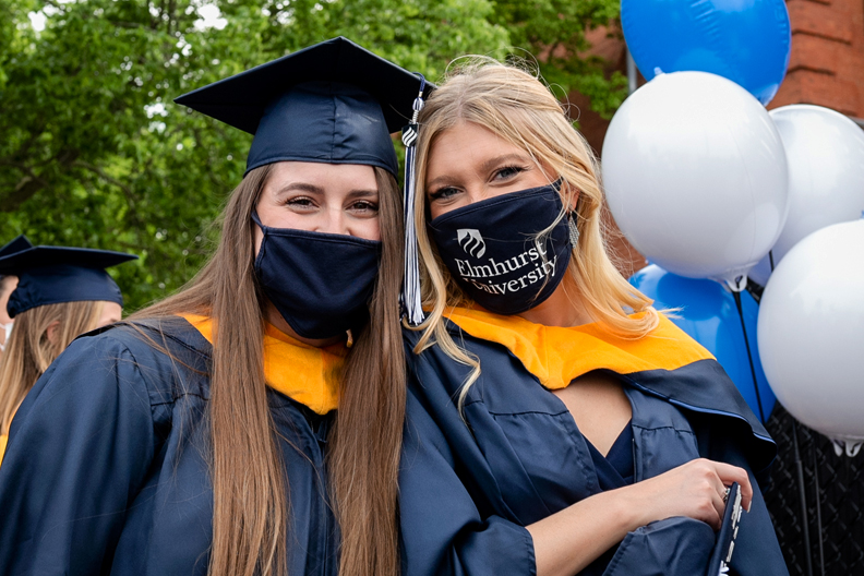 Two graduate students smile before their Commencement ceremony on Friday, May 21, 2021