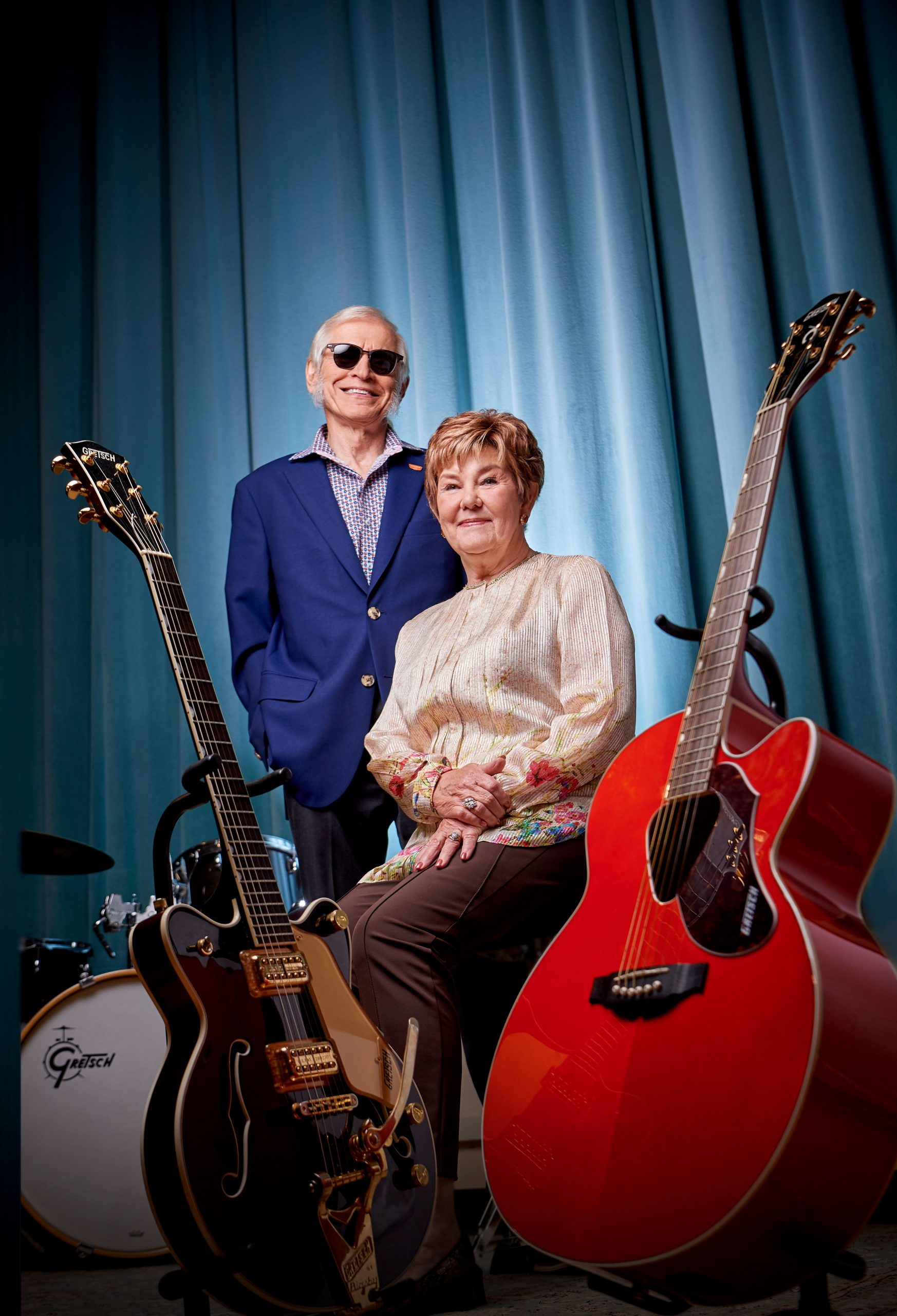 Elmhurst University alumnus Fred Gretsch and wife Dinah Gretsch pose for a photograph with guitars made by their company.