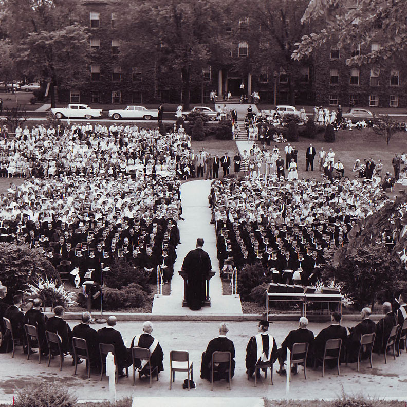 The Elmhurst University 1959 Commencement ceremony, with graduates and other attendees seated on the campus Mall.