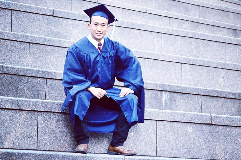 Elmhurst University alumnus Allen Riquelme, wearing his graduation cap and gown.