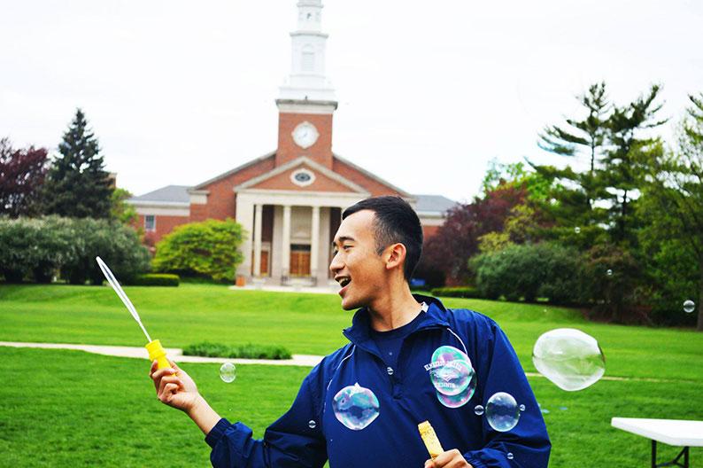 Elmhurst University alumnus Allen Riquelme blows bubbles with a bubble wand on the Mall on Elmhurst University's campus..