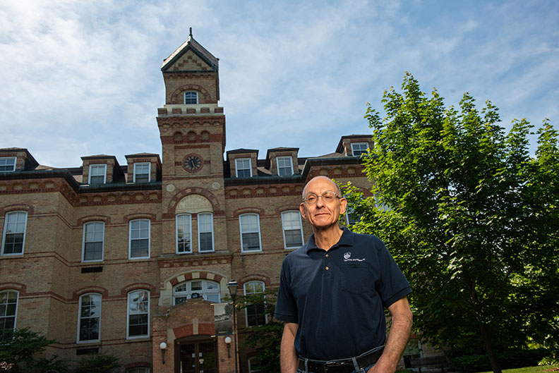 Mark Wakely, Services Manager at Elmhurst University, in front of the Old Main building on campus.