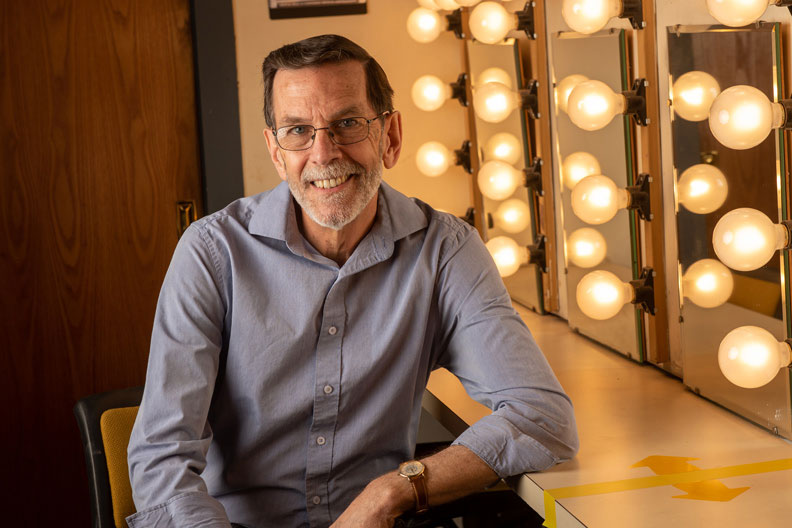 Elmhurst University faculty member Alan Weiger, chair of the Department of Theatre and Dance, sits in the dressing room of Elmhurst's Mill Theatre.