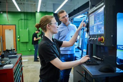 A female Elmhurst University student uses a Tormach prototyping machine in the Elmhurst University Maker Space.