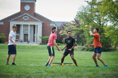 Four male Elmhurst University students play Spikeball on the grass of the campus Mall, with Hammerschmidt Memorial Chapel in the background.