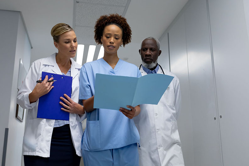 Photo of a nurse flanked by two other medical professionals, looking at a folder with medical information.