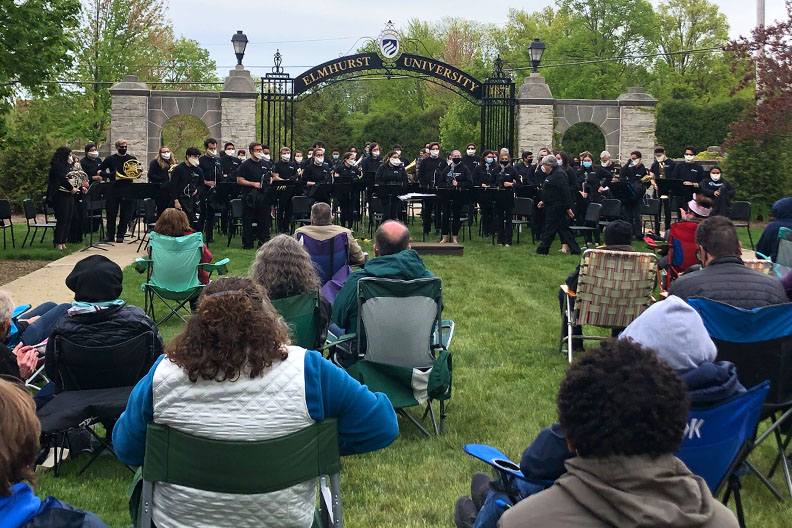 The Elmhurst University Band playing an outdoor concert in front of the Gates of Knowledge for an audience.