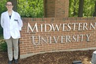 """Katie Martin stands in front of a brick sign reading """"Midwest University."""""""
