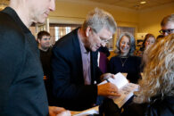 PBS travel TV host Rick Steves signs a book during a speaking engagement at Elmhurst University in 2018.