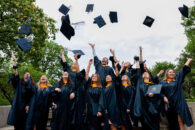 A large group of Elmhurst University graduate students throws their hats up into the air to celebrate their graduation after the 2021 Commencement ceremony.