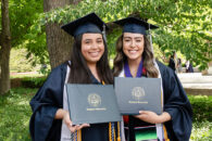 Two female Elmhurst University graduates hold up their degrees following the 2021 Commencement ceremony.