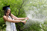 A female Elmhurst University graduate pops open a bottle of champagne following the 2021 Commencement ceremony.