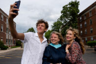 An Elmhurst University graduate student poses for a selfie with others after the 2021 Commencement ceremony.