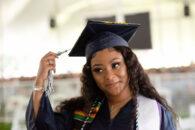 A female Elmhurst University graduate holds the tassel on her cap during the 2021 Commencement ceremony.