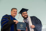 A male Elmhurst University graduate receives his degree onstage during the 2021 Commencement ceremony.