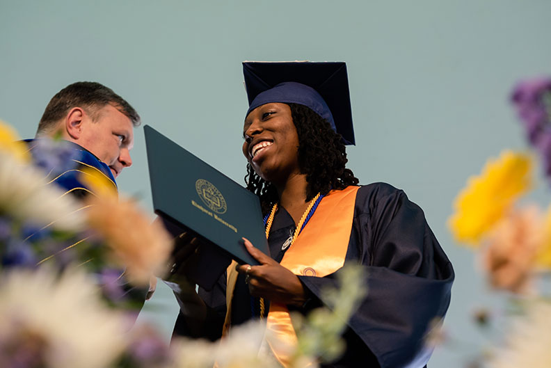 A female Elmhurst University graduate receives her degree onstage during the 2021 Commencement ceremony.