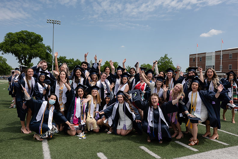 A large group of Elmhurst University graduates pose for a photo on the Langhorst football field for the 2021 Commencement ceremony.